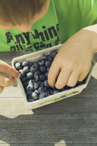 Healthy Kid eating Blueberries